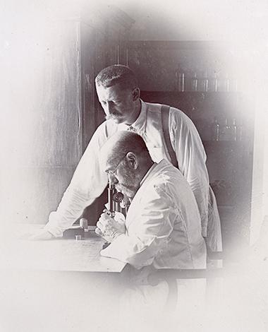 Роберт Кох (у микроскопа) и его коллега Ричард Фридрих Иоганнес Пфайффер (стоит) расследуют вспышку холеры в Бомбее, Индия